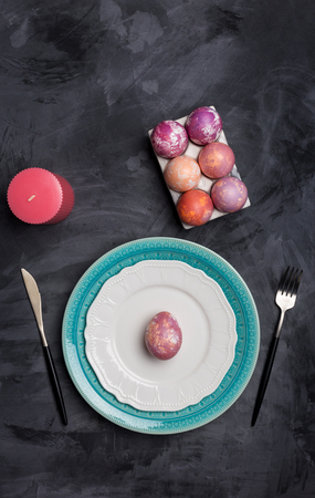 Serving plate for Easter and other holidays. Fork and knife on white and blue plates, pink egg on plate at dark background, Eggs holder and pink candle near. Concept of holiday table setting
