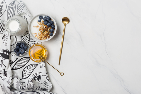 Free space for text with granola, blueberries, honey and yogurt, spoon and napkin. Ingredients for healthy breakfast, concept of diet food, flat lay, table top