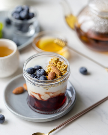 Fresh healthy breakfast with granola with jam and yogurt in jar with blueberries, with tea and honey near on white background Imagens - 122729660