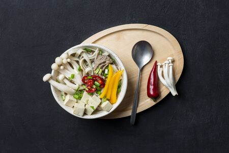 Hot Japanese noodle soup with beef, yellow paprika, mushrooms, green onion, tofu and chili on black background with spoon and wooden tray. Concept of asian soup Stock Photo
