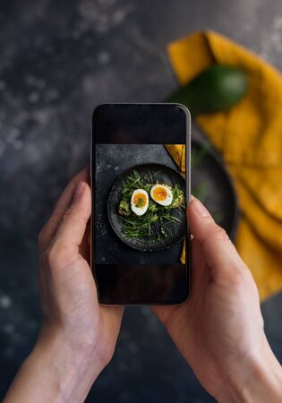 Woman taking photo of sandwich with eggs at black plate with orange napkin at dark background. First person view Banque d'images