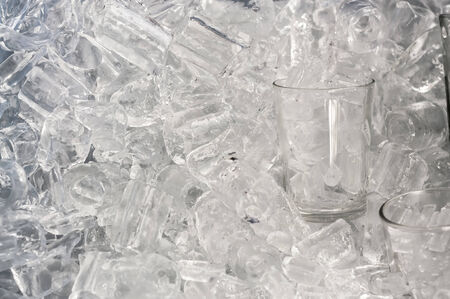 Glass of ice in ice background photo