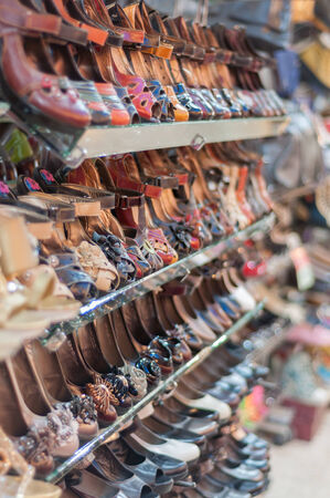 Rows of womens shoes on store shelves.  photo