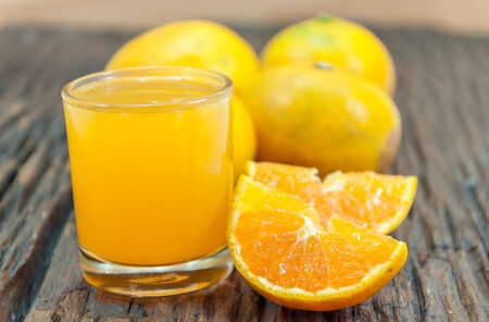 pices: glass of orange juices with some pices of oranges on wood background Stock Photo