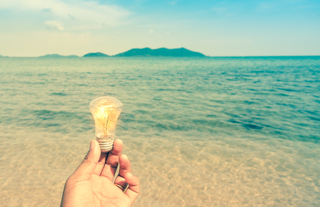 Retro style of man holding lightbulb on the beach with mountain and blue sky as background, Nature conservation concept