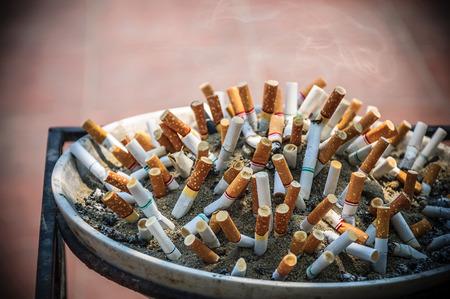 Zigarettenkippe auf Aschenbecher mit Sand und Zigarettenstummeln im Freien