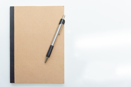 Business concept - Top view  of  notebook cover with pen on empty background for mockup