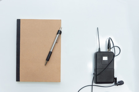 Business concept - Top view  of  notebook cover with pen and portable microphone on empty background for mockup