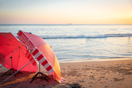 Red umbrella on the beach among  sunset on the sea.
