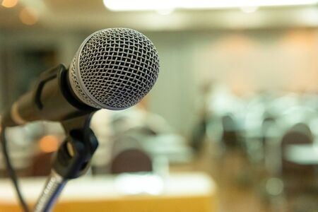 Microphone on abstract blurred background of seminar room or speaking conference.