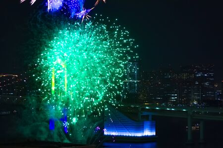 A night fireworks near Rainbow bridge at the urban city long shot. Koutou district Odaiba Tokyo Japan - 12.07.2019 : It s a city location in Tokyo.