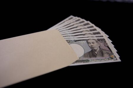 Japanese currency 100,000 yen with envelope on the black background closeup