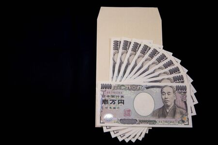 Japanese currency 100,000 yen with envelope on the black background copyspace