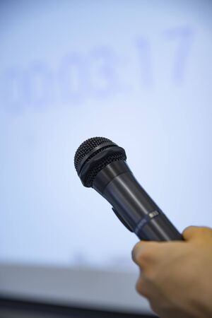 A microphone with left hand behind the white board at the office