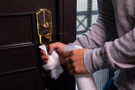 Disinfecting door knob by cleaner at the entrance Standard-Bild