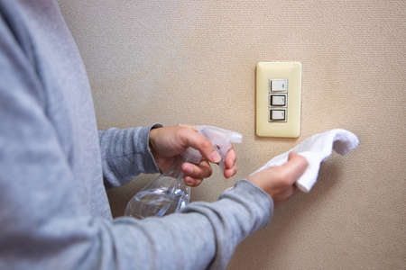 Disinfecting and wiping switch by male hand closeup daytime
