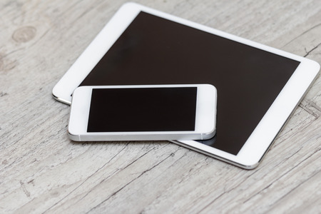 modern palmtop: smartphone and tablet on the gray wooden background - concept Stock Photo