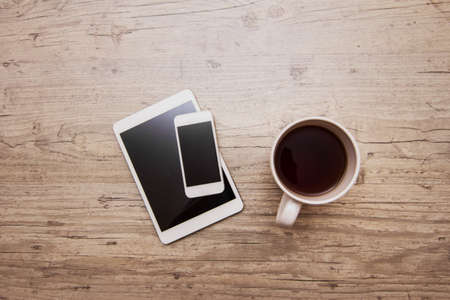 palmtop: cup of coffee, smart phone and tablet on gray wooden background