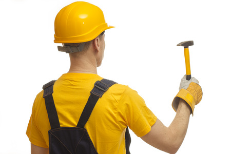 builder in a yellow T-shirt, in the yellow helmet with a hammer