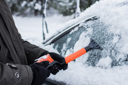 car, winter, people and vehicle concept - closeup of man pushing car stuck in snow Stock Photo