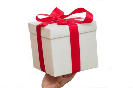 White gift box with a red ribbon on a white background