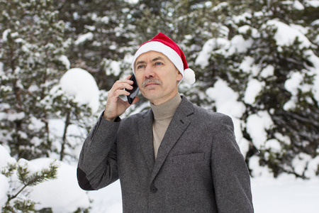 close-up of a businessman in winter in the forest with a phone in a gnome cap Stock Photo