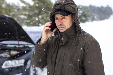 Car, winter, people and vehicle concept - Close-up the driver in the winter on the road calls for help by phone