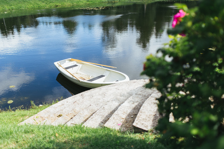 Boat with oars on the stone ancient stairs on the shore of a small lake Banco de Imagens