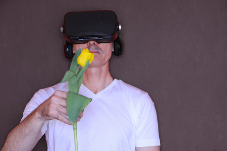 Close-up - a man with glasses of virtual reality gives a yellow tulip of virtual love