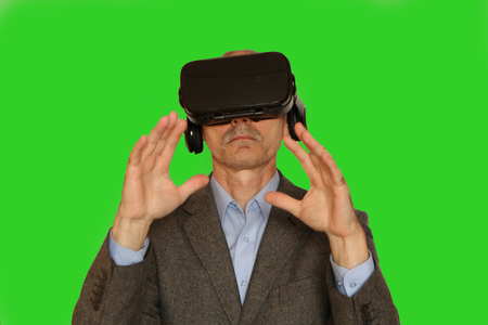 Close-up of a man in a suit with glasses of virtual reality. The background is green. Stockfoto