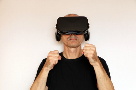 Close-up of a man in a black T-shirt with glasses of virtual reality. The background is white.
