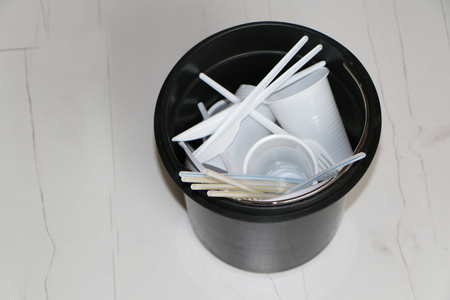 Disposable plastic dishes in the trash. The ban on the use of disposable tableware. The problem of waste - the dark side of the abundance of disposable disposable tableware in the world.