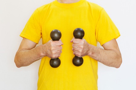 Close-up - a man in a yellow T-shirt doing exercises with dumbbells Stock Photo