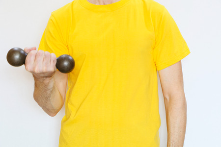 Close-up - a man in a yellow T-shirt doing exercises with dumbbells Banco de Imagens