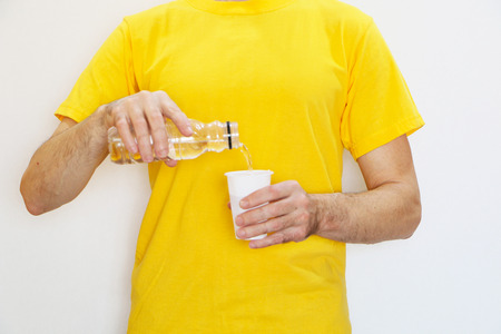 Close-up - a man in a yellow T-shirt pours water from a plastic bottle into a plastic cup
