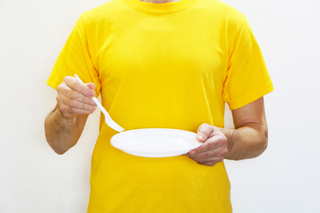 Close-up - a man in a yellow T-shirt eats from plastic dishes and hurts his health