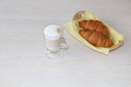 Close-up - breakfast, a cup of cappuccino coffee and croissants on the table. The background is light. Stock Photo