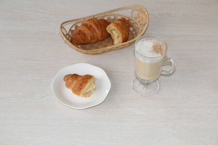 Close-up - breakfast, a cup of coffee and croissants on the table. The background is light.