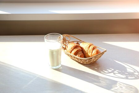 A healthy breakfast in the morning with a crissant and with milk in a laid glass