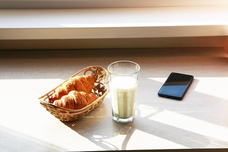 A wholesome business breakfast with croissant, with milk, with a telephone.