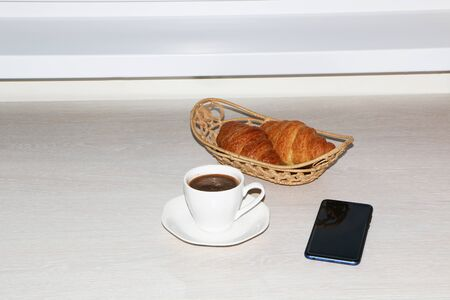 Business French breakfast with croissant. On the table is a smartphone.