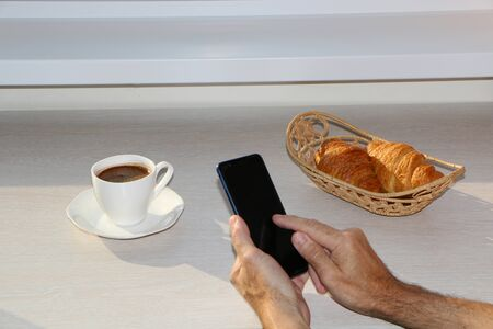 Business breakfast with a croissant, with coffee, a telephone in his hands.