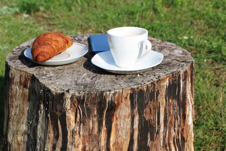 Woman in the summer has breakfast in a summer cafe with a cup of coffee, croissant and a smartphone