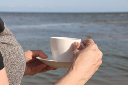 Girl with a croissant and a cup of coffee on the sandy seashore
