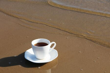 A cup of aromatic coffee stands romantically on the seashore Banco de Imagens