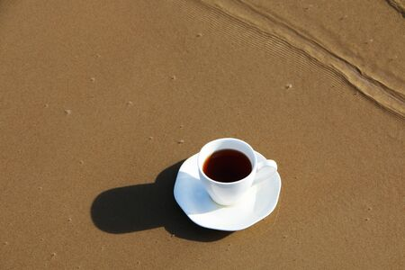A cup of aromatic coffee stands romantically on the seashore Stock Photo