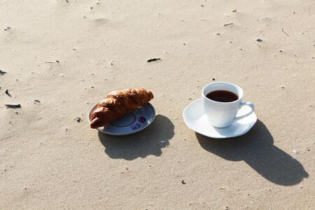 A cup of coffee with a delicious croissant stands on the sandy seashore