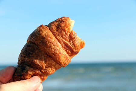 Close-up - tasty beautiful croissant in hand on a background of the sea Фото со стока