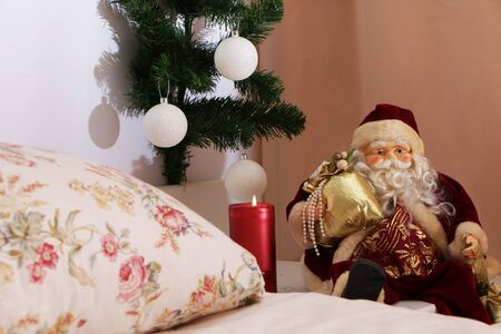 At Christmas, Santa Claus sits with a gift near the bed next to a burning candle, an elegant Christmas tree is soaking.