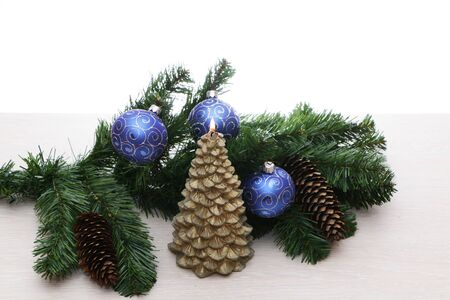 Blue christmas tree decorations with green spruce branch. The background is light.